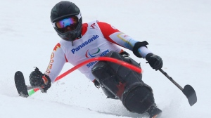 Josh Dueck of Canada races during men's super combined, slalom, sitting event at the 2014 Winter Paralympic, Tuesday, March 11, 2014, in Krasnaya Polyana, Russia. (AP Photo/Dmitry Lovetsky)