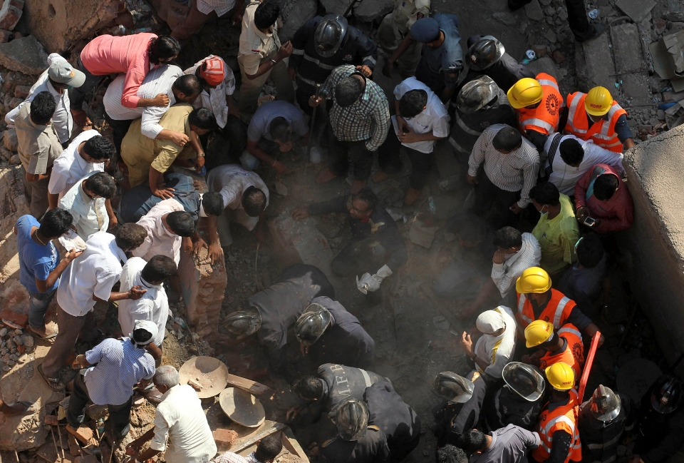 Rescue workers search for survivors in the debris of a building that collapsed in Mumbai, India, Friday, March 14, 2014. (AP / Rafiq Maqbool)