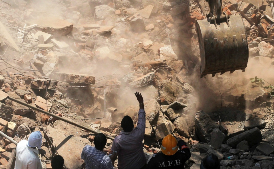 A crane clears debris of a building that collapsed to look for survivors in Mumbai, India, Friday, March 14, 2014. (AP / Rafiq Maqbool)