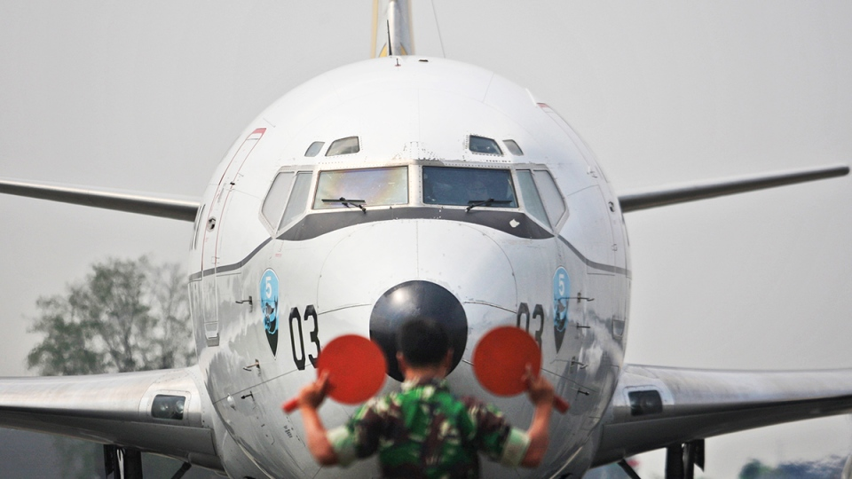 "A marshall directs an Indonesian Air Force Boeing 737 ""Surveiller"" of the 5th Air Squadron ""Black Mermaids"" to park on the tarmac following a search operation for the missing Malaysia Airlines Boeing 777 that was conducted over the Strait of Malacca, at Suwondo air base in Medan, North Sumatra, Indonesia, Friday, March 14, 2014. (AP / Binsar Bakkara)"