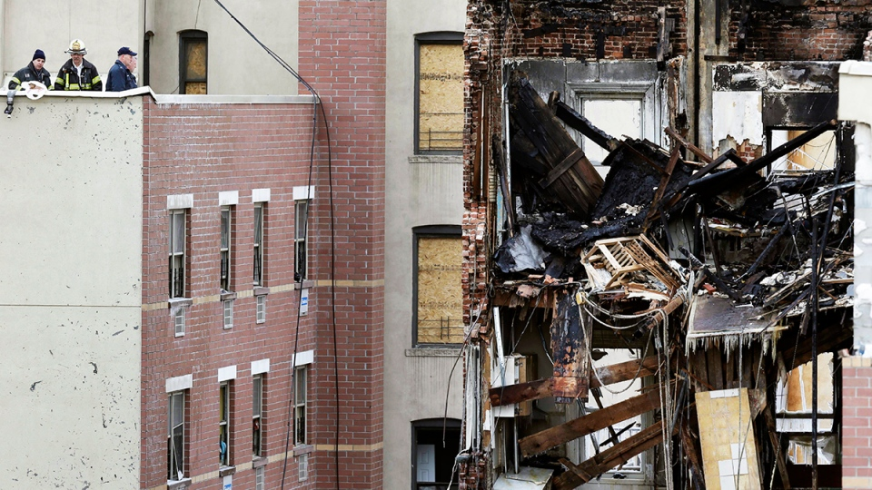 Firefighters look over the site of a building explosion in New York, Friday, March 14, 2014. (AP / Seth Wenig)