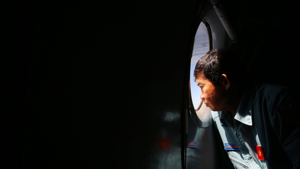Officer Lang Van Ngan of the Vietnam Air Force looks out the window onboard a flying AN-26 Soviet made aircraft during a search operation for the missing Malaysia Airlines flight MH370 plane over the southern sea between Vietnam and Malaysia Friday, March 14, 2014. (AP / Na Son Nguyen).