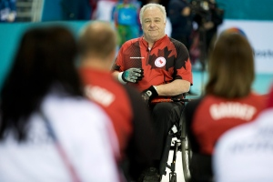 Canada's skip Jim Armstrong, center, smiles during the wheelchair curling match between Canada and Norway at the 2014 Winter Paralympics in Sochi, Russia, Monday, March 10, 2014. Norway won 8-6. (AP / Pavel Golovkin