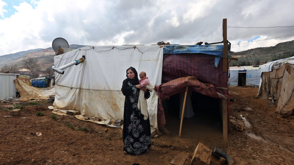 In this Tuesday, March 11, 2014 photo, Mervat, 31, stands outside of her tent as she holds her 9-month-old daughter Shurouk, at camp for Syrian refugees camp in Kab Elias, in Lebanon's Bekaa Valley. (AP / Bilal Hussein)