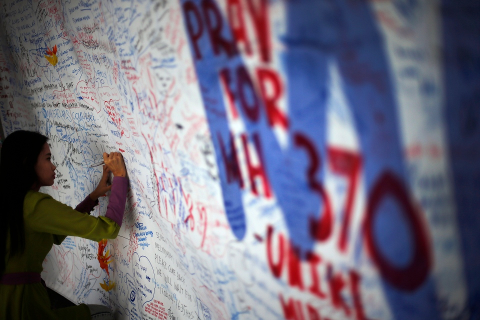 A woman writes on a board of messages and well-wishes dedicated to people involved with the missing Malaysia Airlines jetliner MH370 in Sepang, Malaysia on March 15, 2014. (AP / Wong Maye-E)