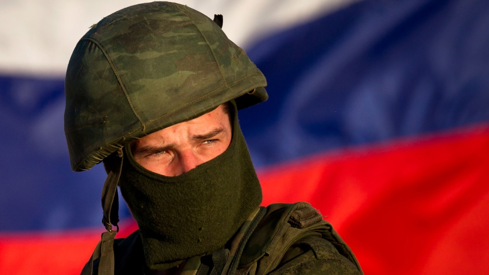 A pro-Russian soldier is back dropped by Russia's flag while manning a machine-gun outside an Ukrainian military base in Perevalne, Ukraine, Saturday, March 15, 2014. (AP / Vadim Ghirda)