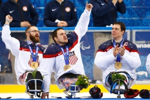United States players Taylor Lipsett, left, Greg Shaw, centre, and Andy Yohe celebrate after winning the gold medal ice sledge hockey match against Russia at the 2014 Winter Paralympics in Sochi, Russia on March 15, 2014. United States won 1-0. (AP Photo/Pavel Golovkin)