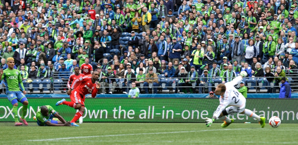 Toronto FC's Jermain Defoe, third from left, kicks a goal past Seattle Sounders goalkeeper Stephan Frei, right, in the first half of an MLS soccer match in Seattle on Saturday, March 15, 2014. (AP / Ted S. Warren)