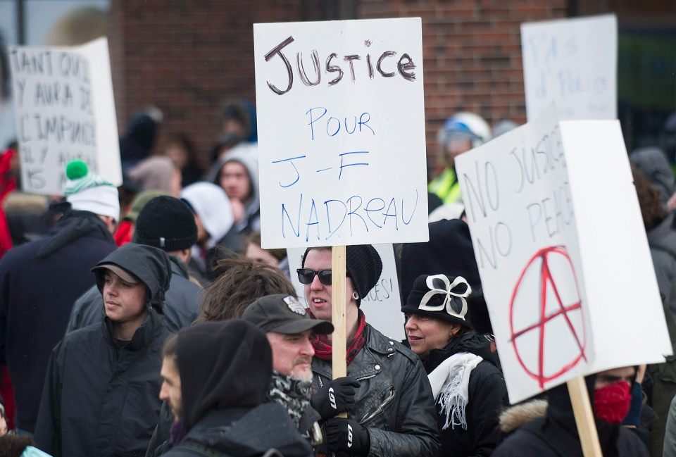 Protesters hold up signs during an anti police brutality demonstration in Montreal Saturday, March 15, 2014. (Graham Hughes / THE CANADIAN PRESS)
