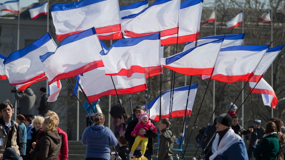 A man holds a child under Crimean flags as pro-Russian people attend a rally in Lenin Square, in Simferopol, Ukraine, Saturday, March 15, 2014. (AP / Vadim Ghirda)