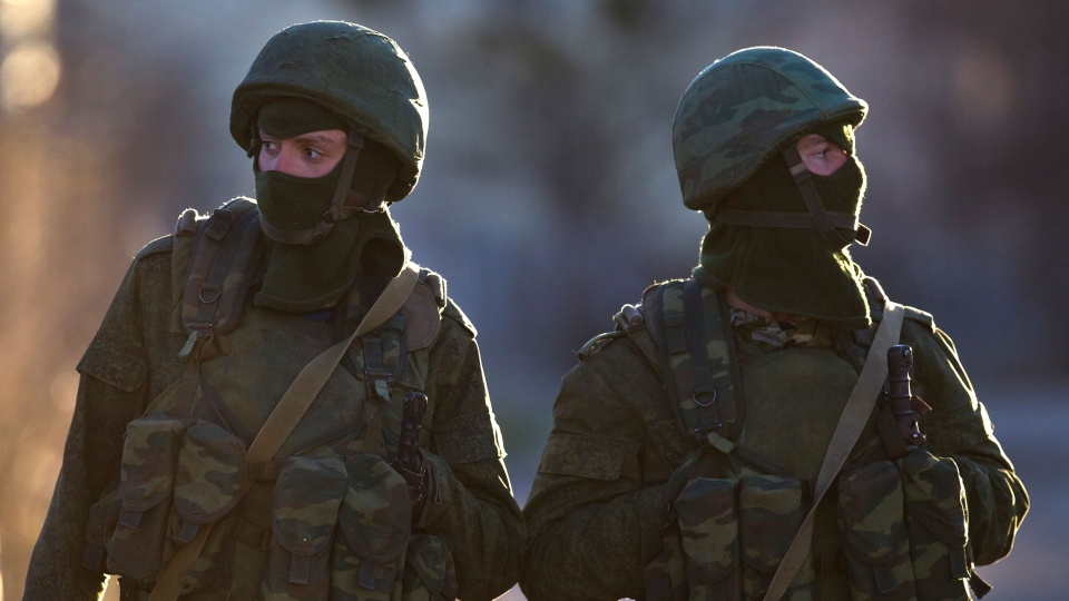 Pro-Russian soldiers stand close to the main gate of an Ukrainian military base in Perevalne, Ukraine, Saturday, March 15, 2014. (AP / Vadim Ghirda)