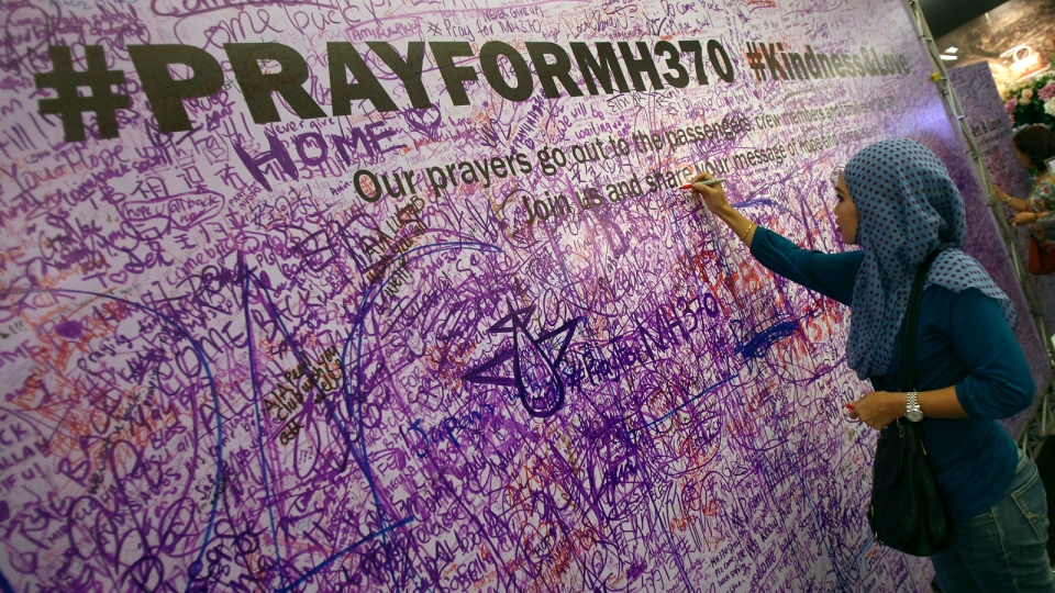 A woman leaves a message for passengers aboard a missing Malaysia Airlines plane, at a shopping mall in Petaling Jaya, near Kuala Lumpur, Malaysia, Sunday, March 16, 2014. Malaysian authorities Sunday were investigating the pilots of the missing jetliner after it was established that whoever flew off with the Boeing 777 had intimate knowledge of the cockpit and knew how to avoid detection when navigating around Asia. (AP / Lai Seng Sin)