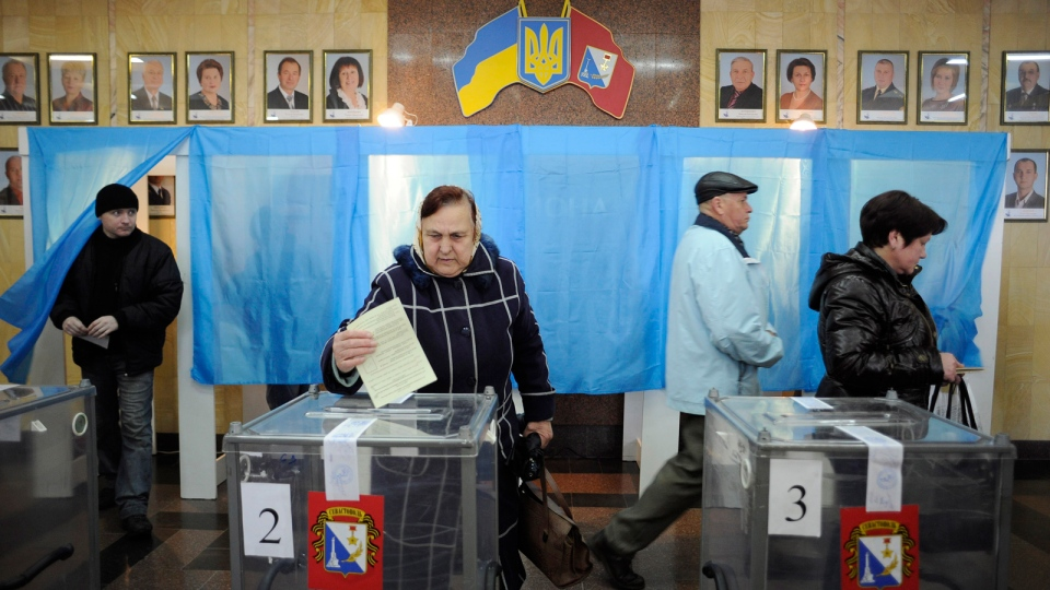 A woman casts her ballot at a polling station during the Crimean referendum, in Sevastopol, Ukraine, Sunday, March 16, 2014. Residents of Ukraine's Crimea region are voting in a contentious referendum on whether to split off and seek annexation by Russia. (AP / Andrew Lubimov)