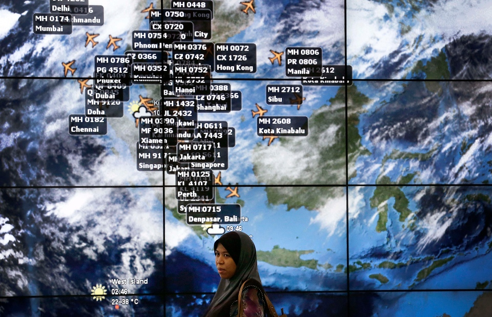 A lady stands in front of an electronic display showing live information of flight positions according to predicted time and flight duration calculations at the Kuala Lumpur International Airport, Sunday, March 16, 2014 in Sepang, Malaysia. (AP / Wong Maye-E)