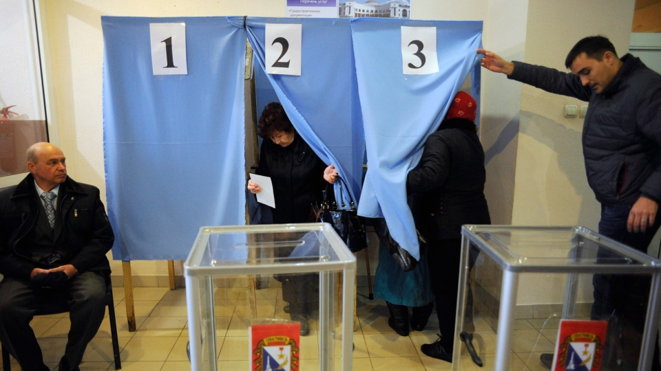 Local residents enter and exit polling booths at a polling station during the Crimean referendum, in Sevastopol, Ukraine, Sunday, March 16, 2014. Residents of Ukraine's Crimea region are voting in a contentious referendum on whether to split off and seek annexation by Russia. (AP / Andrew Lubimov)