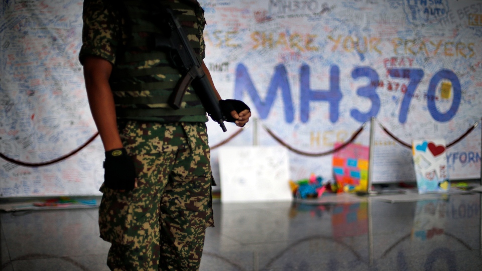 A Malaysian military soldier patrols the viewing gallery of the Kuala Lumpur International Airport where dedication boards with well wishes and messages for people involved with the missing Malaysia Airlines jetliner MH370 is displayed, Sunday, March 16, 2014 in Sepang, Malaysia. (AP / Wong Maye-E)