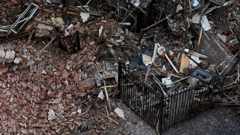 Workers survey an area covered in rubble Friday, March 14, 2014, two days after a natural gas explosion leveled two apartment buildings in New York. (AP Photo/Julio Cortez)