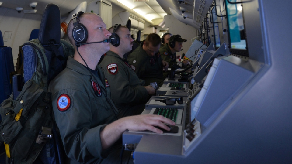 Crew members on board an aircraft P-8A Poseidon assist in search and rescue operations for Malaysia Airlines flight MH370 in the Indian Ocean on Sunday, March 16, 2014. (U.S. Navy / Eric A. Pastor)