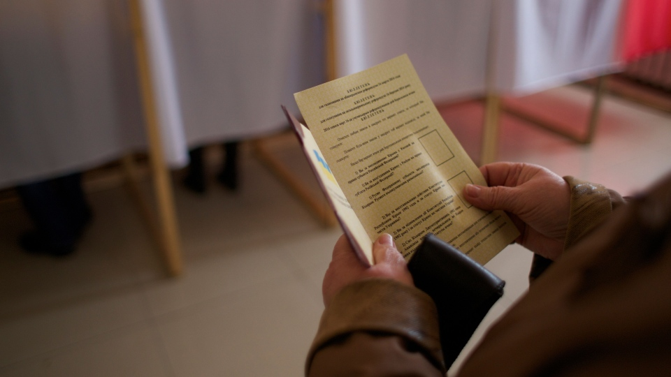 A woman holds a ballot before voting at a polling station in Simferopol, Ukraine, on Sunday, March 16, 2014. (AP / Ivan Sekretarev)
