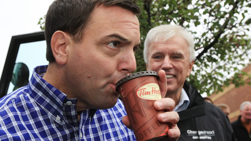 Ontario Conservative Leader Tim Hudak has a drink of Tim Hortons coffee with Chatham-Kent-Essex candidate Rick Nicolls at a campaign stop in Blenheim, Ontario, Monday, Oct. 3, 2011. (Dave Chidley / THE CANADIAN PRESS)