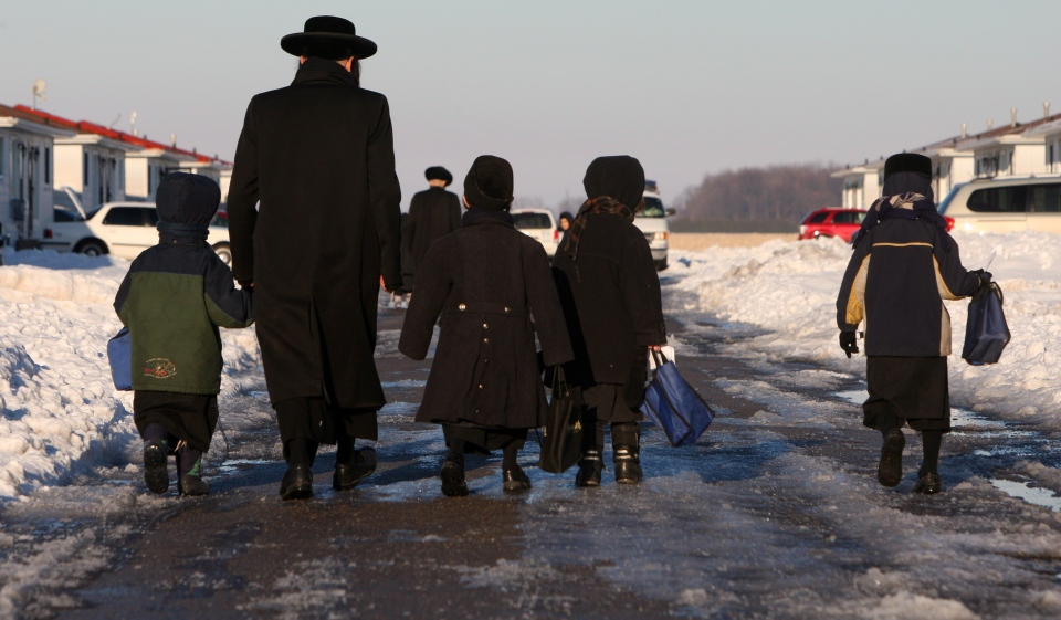 Members of the Lev Tahor ultra-orthodox Jewish community walk children home from school in Chatham, Ont., on Monday, Feb. 3, 2014. (The Canadian Press/Dave Chidley)