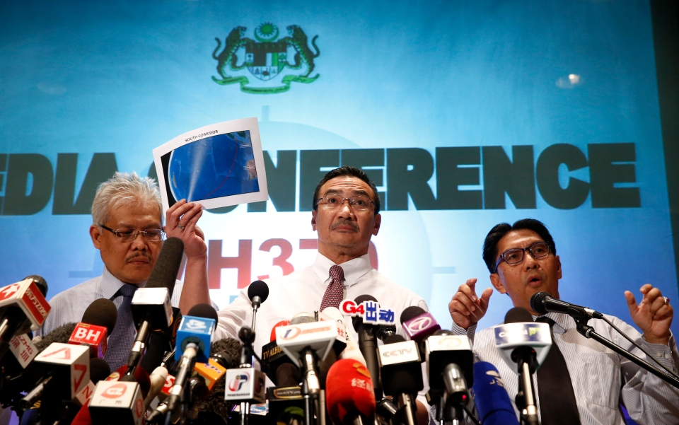 Malaysian acting Transport Minister Hishamuddin Hussein, centre, shows maps of South Corridor and North Corridor of the search and rescue as director general of the Malaysian Department of Civil Aviation, Azharuddin Abdul Rahman, right, and Malaysian Deputy Foreign Minister Hamzah Zainudin during a press conference at a hotel next to the Kuala Lumpur International Airport, in Sepang, Malaysia, Monday, March 17, 2014. (AP / Vincent Thian)