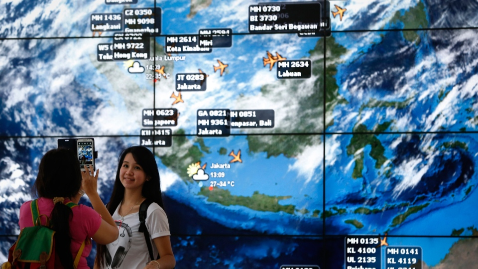 An electronic display shows live information of flight positions according to predicted time and flight duration calculations at the Kuala Lumpur International Airport, in Sepang, Malaysia, Monday, March 17, 2014. (AP / Vincent Thian)