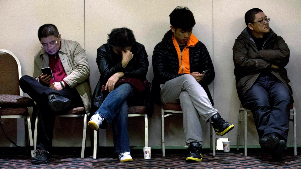 Relatives of Chinese passengers aboard the missing Malaysia Airlines Flight MH370 wait for a news briefing held by the airlines' officials at a hotel ballroom in Beijing Monday, March 17, 2014. (AP / Andy Wong)