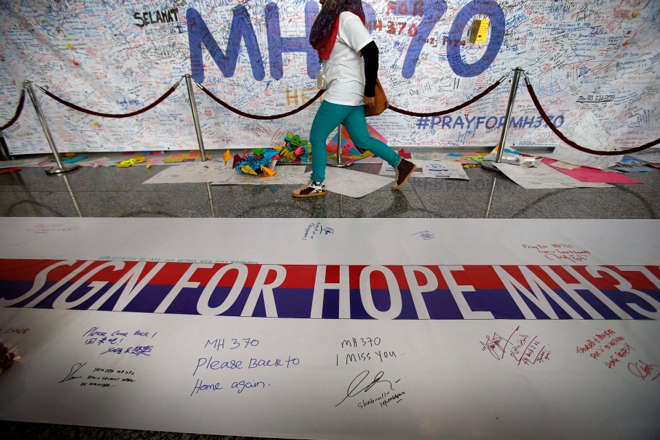 A woman walks past a banner filled with signatures and well-wishes for all involved with the missing Malaysia Airlines jetliner MH370 at the Kuala Lumpur International Airport in Sepang, Malaysia, Sunday, March 16, 2014. (AP / Wong Maye-E)