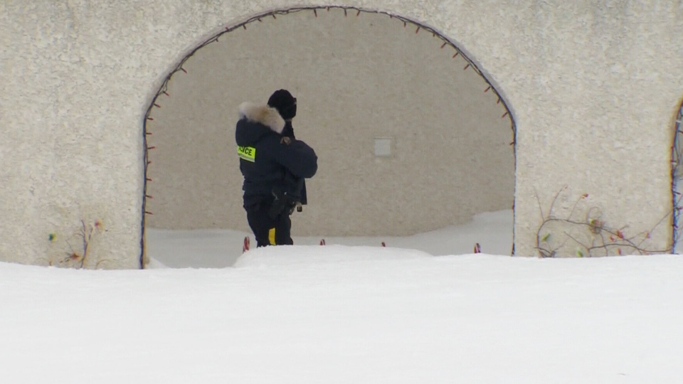 Police are seen outside of a residence where a 7-year-old girl was killed after she was mauled by two dogs in Manitoba, Sunday, March 16, 2014.