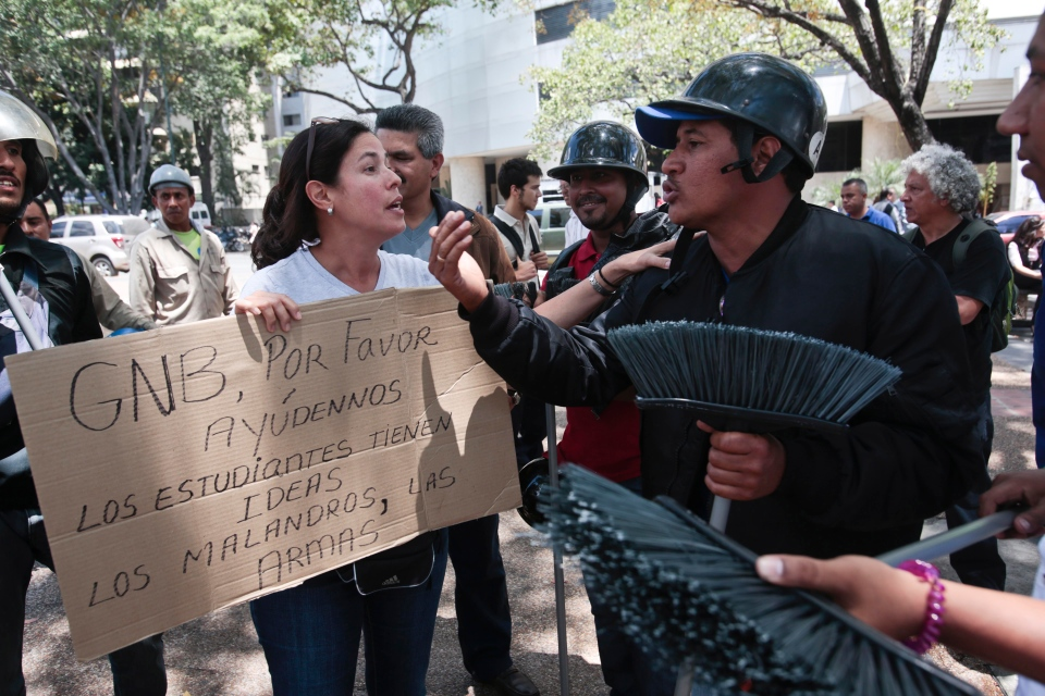 A anti-government demonstrator, left, argues with a pro-government supporter inside of Plaza Altamira in Caracas, Venezuela, Monday, March 17, 2014.(AP / Esteban Felix)