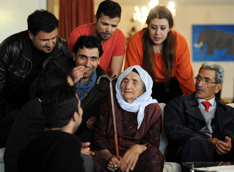 107-year-old Syrian Sabria Khalaf, center, sits on a sofa with members of her family in Holdorf, northern Germany, Monday, March 17, 2014. (AP / dpa, Ingo Wagner)