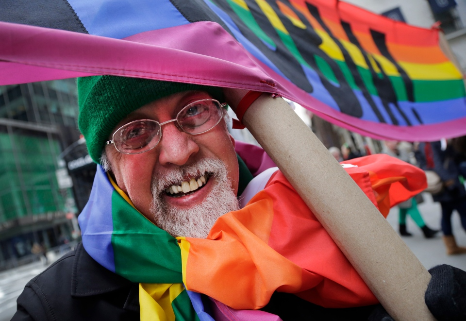 "Artist Gilbert Baker, designer of the Rainbow Flag, is draped with the flag while holding a banner that reads ""Boycott Homophobia"" before the start of the St. Patrick's Day parade in New York, Monday, March 17, 2014. (AP / Mark Lennihan)"
