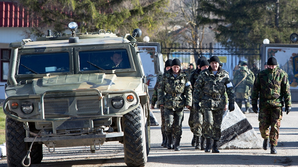 Ukrainian troops with white bands on their sleeves march past an unmarked Russian military vehicle outside a Ukrainian military base in Perevalne, Crimea, Ukraine, Monday, March 17, 2014. (AP / Andrei Udovichenko)