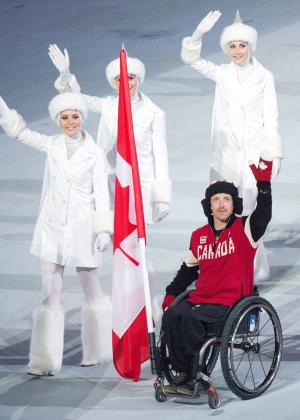 Canadian Paralympic skier Josh Dueck carries the Canadian flag into the closing ceremonies at the 2014 Paralympic Winter Games in Sochi, Russia, Sunday, March 16, 2014. (/HO-Canadian Paralympic Committee-Matthew Murnaghan / THE CANADIAN PRESS)