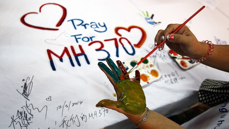 A woman paints her palm with water colors during an event for passengers aboard a missing Malaysia Airlines plane, in Kuala Lumpur, Malaysia, Monday, March 17, 2014. (AP / Lai Seng Sin)