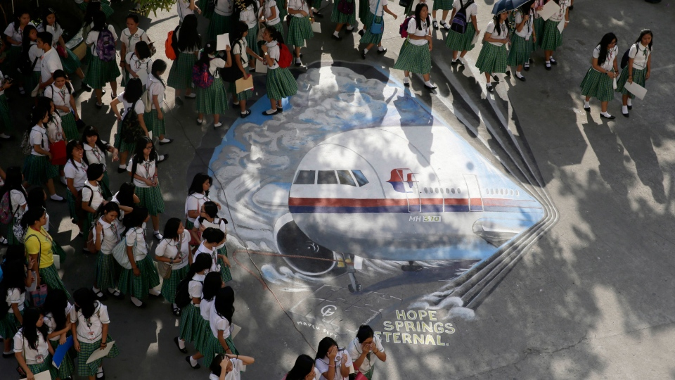 Students from the Benigno Aquino High School walk on a mural depicting the missing Malaysia Airlines plane at their campus at Makati city, east of Manila, Philippines, Tuesday, March 18, 2014. (AP / Bullit Marquez)