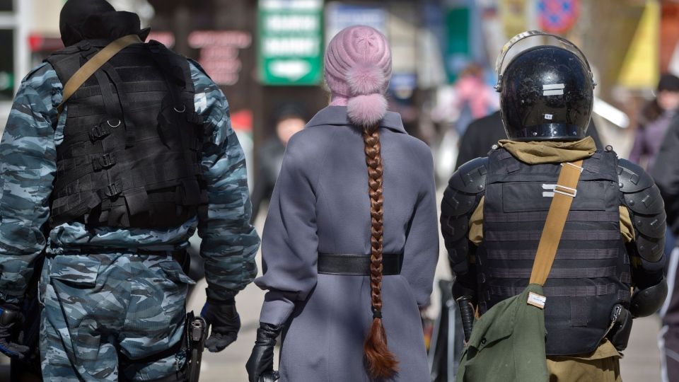 A woman walks between armed men in riot gear, that were performing identity and hand bag checks on people walking near the building of Crimea's regional parliament in Simferopol, Ukraine, Monday, March 17, 2014. (AP / Vadim Ghirda)