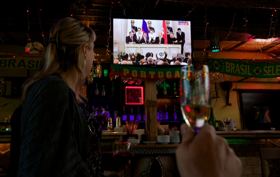Residents prepare to toast as they watch a live broadcast from Moscow showing the signing of documents on Russia's annexation of Crimea, in Simferopol, Ukraine, on Tuesday, March 18, 2014. (AP / Ivan Sekretarev)