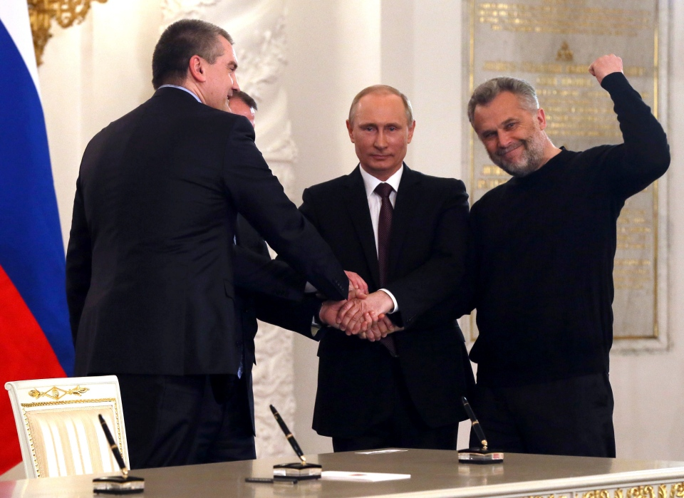 Russian President Vladimir Putin, second right, Speaker of Crimean legislature Vladimir Konstantinov, second left partly visible, Crimean Premier Sergei Aksyonov, left, and Sevastopol mayor Alexei Chalyi, right, shake hands after signing a treaty for Crimea to join Russia in the Kremlin in Moscow, Tuesday, March 18, 2014. (AP / Sergei Ilnitsky, Pool)
