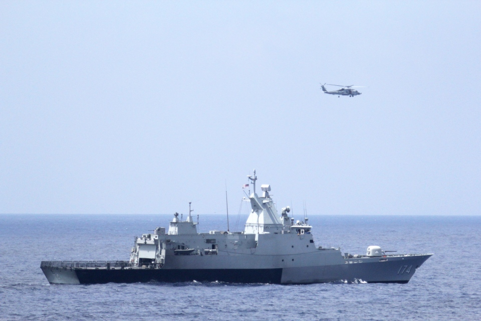 This photo provided by the U.S. Navy shows the Royal Malaysian Navy corvette KD Terengganu and a U.S. Navy MH-60R Sea Hawk helicopter conduct a coordinated air and sea search for a missing Malaysian Airlines jet in the Gulf of Thailand. (AP Photo/U.S. Navy, Operations Specialist 1st Class Claudia Franco)