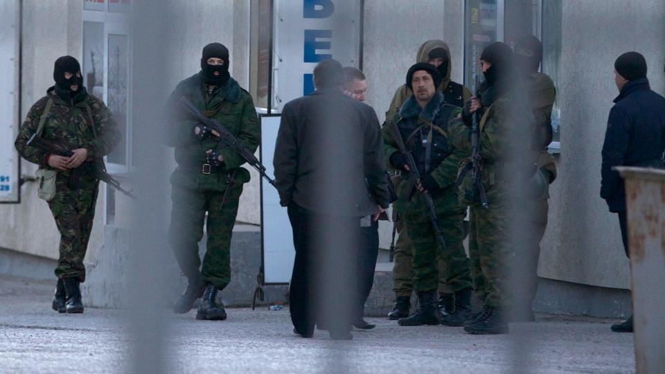 Unidentified armed men walk at a area close to an Ukrainian military unit in Simferopol, Crimea, on Tuesday, March 18, 2014. (AP / Ivan Sekretarev)
