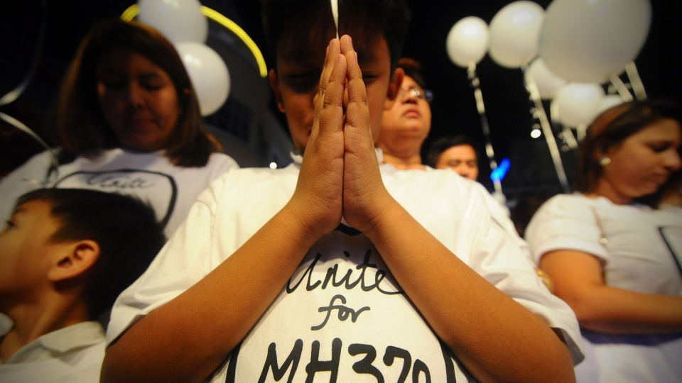 A young Malaysian boy prays, at an event for the missing Malaysia Airline, MH370, at a shopping mall, in Petaling Jaya, on the outskirts of Kuala Lumpur, Malaysia, Tuesday, March 18, 2014. (AP / Joshua Paul)