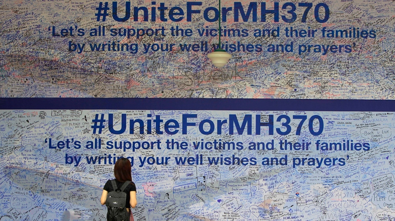 A woman reads messages for passengers aboard a missing Malaysia Airlines plane, at a shopping mall in Petaling Jaya, near Kuala Lumpur, Malaysia, Tuesday, March 18, 2014. (AP / Lai Seng Sin)