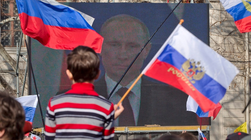 A child holds a Russian flag backdropped by a large screen showing a broadcast of Russian President Vladimir Putin's speech on Crimea, in Sevastopol, Crimea, Tuesday, March 18, 2014. (AP Photo/Vadim Ghirda)