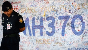 A police officer stands in front of messages board for the passengers aboard a missing Malaysia Airlines plane at Kuala Lumpur International Airport in Sepang, Malaysia, Wednesday, March 19, 2014. (AP / Vincent Thian)