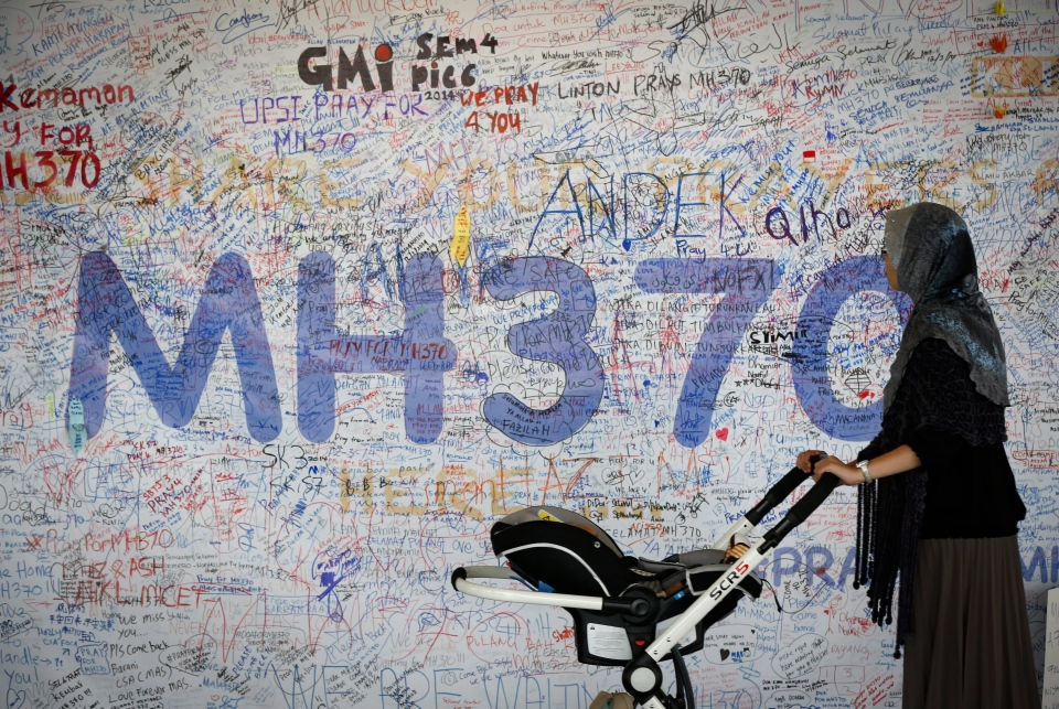 A woman pushes her baby cart in front of the messages board for passengers aboard a missing Malaysia Airlines plane at Kuala Lumpur International Airport in Sepang, Malaysia, Wednesday, March 19, 2014. (AP / Vincent Thian)