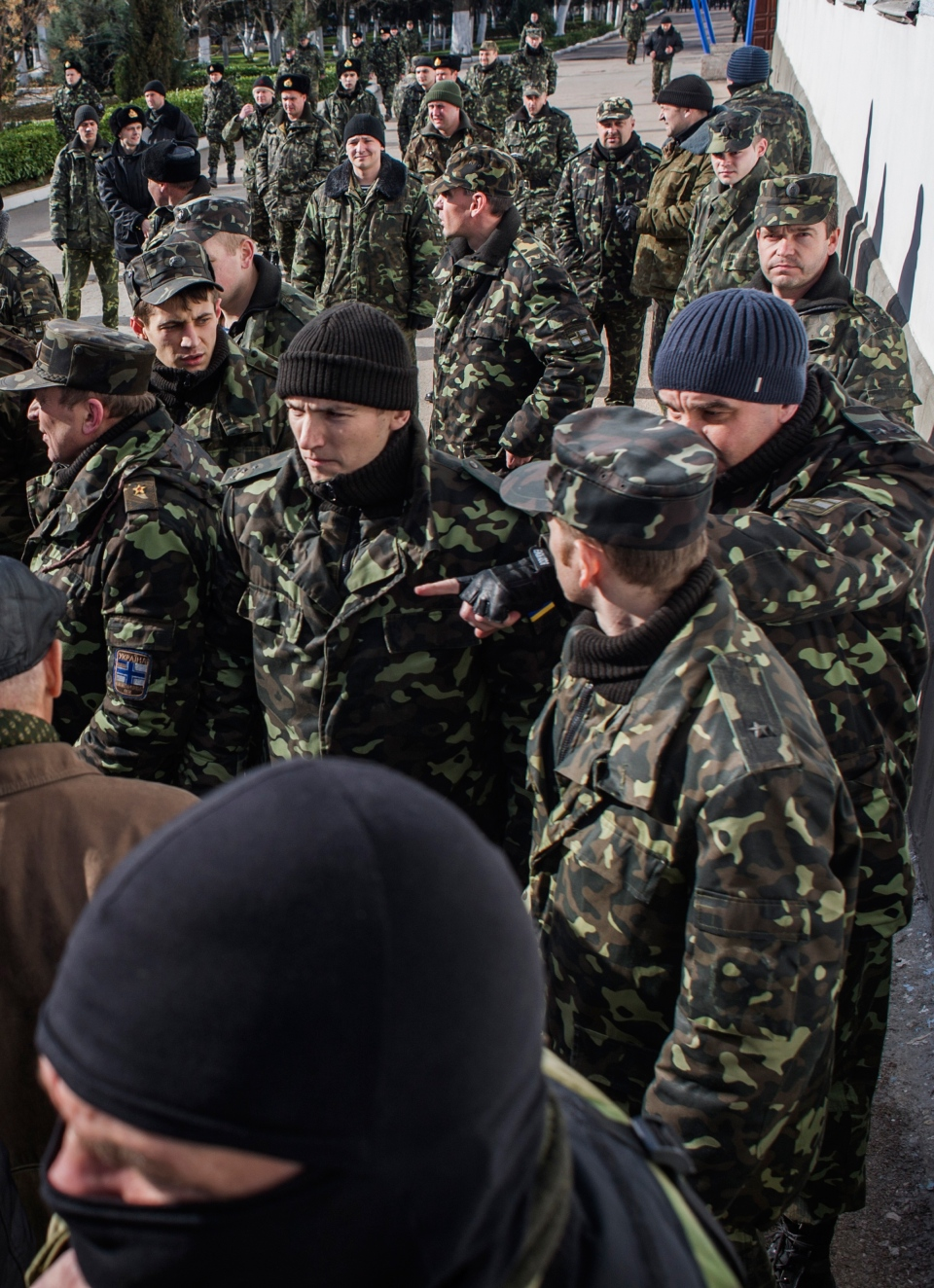 Ukrainian servicemen stand, with a Crimean self-defense forces member in front, outside the Ukrainian navy headquarters in Sevastopol, Crimea, Wednesday, March 19, 2014. (AP / Andrew Lubimov)