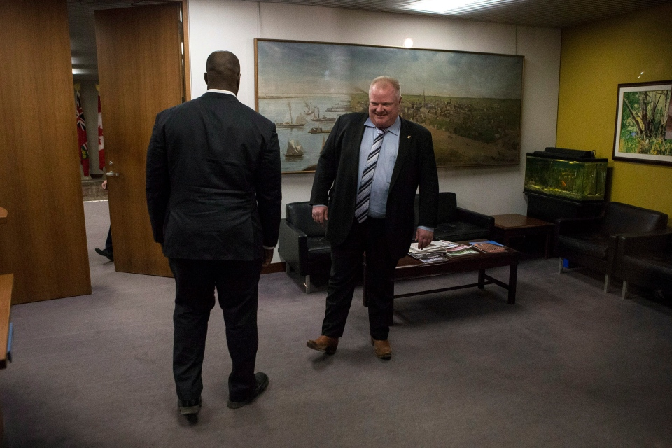 Toronto Mayor Rob Ford, right, steps out of his office at city hall on Wednesday, March 19, 2014. THE CANADIAN PRESS/Chris Young