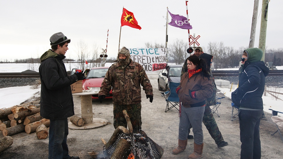 First Nations protesters stand around a fire during a protest to block the Via Rail tracks and Wyman's Road near Shannonville, Ont., on Wednesday, March 19, 2014. (Lars Hagbergg / THE CANADIAN PRESS)